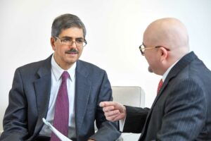 Amitabh Dugar, PhD, CPA sitting and speaking with Jacob Pozharny, PhD